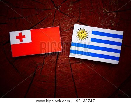 Tongan Flag With Uruguaian Flag On A Tree Stump Isolated