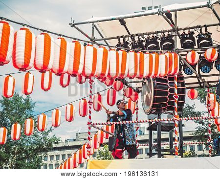 Moscow Russia - July 16 2017: Musicians ASKA-GUMI play the taiko drums on scene yagura During the japanese festival. Paper red-white lanterns Chochin Scenery for the holiday Obon
