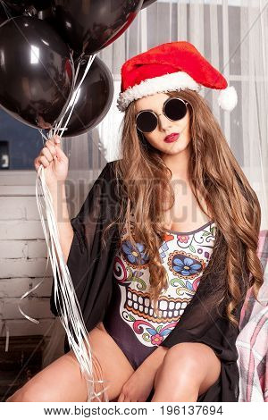 Attractive girl posing for camera wearing combination, red hat and glasses. Woman holding a bungle of baloons.