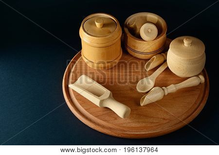 Wooden containers for products, spoon, cup, pestle, mortar on wooden board. Free space for text. Black background.