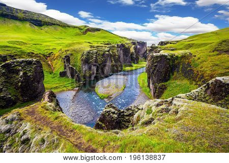 Magic canyon Fyadrarglyufur. Green Icelandic Tundra in July. Bizarre shape of cliffs and stream with glacial water. The concept of active northern tourism