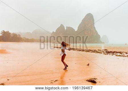 Rain. Woman enjoying rainy fall day on Thailand tropical beach. Young smiling woman in white