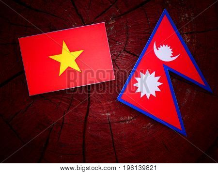 Vietnamese Flag With Nepali Flag On A Tree Stump Isolated