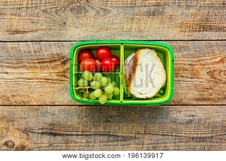 healthy break with cherry tomatoes, grapes and sandwich in green lunchbox on wooden table background, flat lay