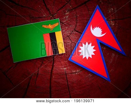 Zambian Flag With Nepali Flag On A Tree Stump Isolated