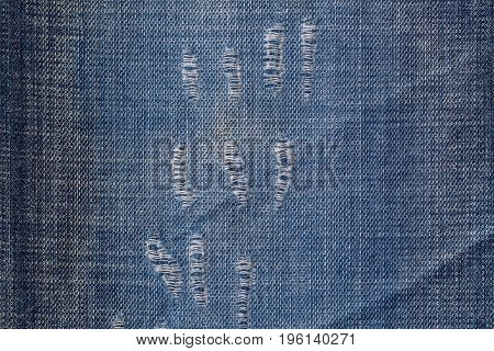 Closeup background of blue denim jeans textile with distressed texture pattern, a few worn out holes