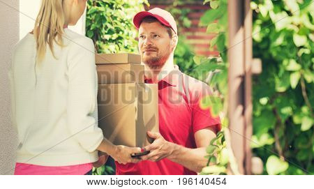 woman accepting a home delivery of boxes from deliveryman. copy space