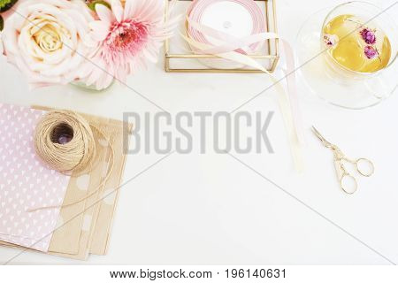 Handmade craft concept. Handmade goods for packaging - twine ribbons. Feminine workplace concept. Freelance fashion femininity workspace in flat lay style with flowers rose tea notebooks on bright background. poster