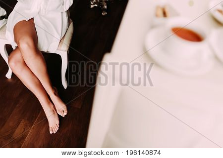 The elegantbride in a white robe is sitting on a chair. Slim and nude legs of a young lady. Morning preparation before the wedding. Side view, horizontal