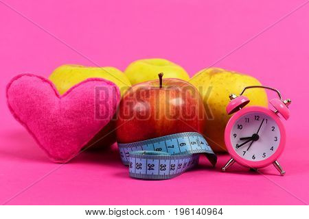 Time for diet. Heart alarm clock and apples with blue measuring tape on pink background. Healthy food and regime valentines day