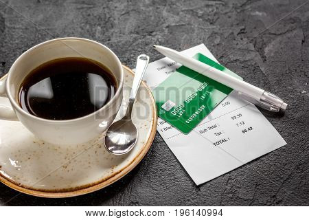 paying check for business lunch in cafe with credit card on dark table background
