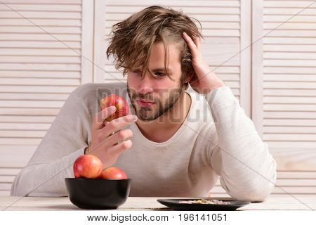 Man at wooden table with bowl of apples and plate of pills. Guy with thoughtful face holds fruit near drugs on light background. Bearded man and food with medicine. Diet and healthy choice concept