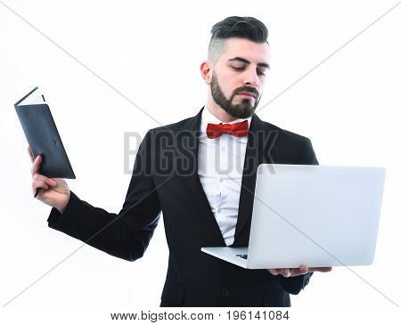 Businessman or insurance agent with beard red bow and concentrated smiling look holds his laptop and paper planner isolated on white background. Concept of online business conference and planning