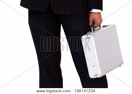 Business man in black suit carrying a hard suitcase isolated.