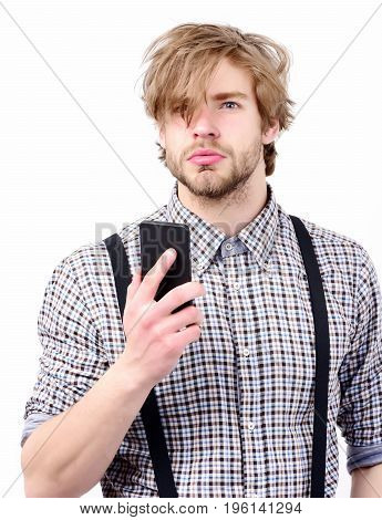 High tech development concept. Man with surprised or thoughtful face beard and stylish hair holds mobile phone. Idea of modern technology. Macho with black gadget in hand isolated on white background