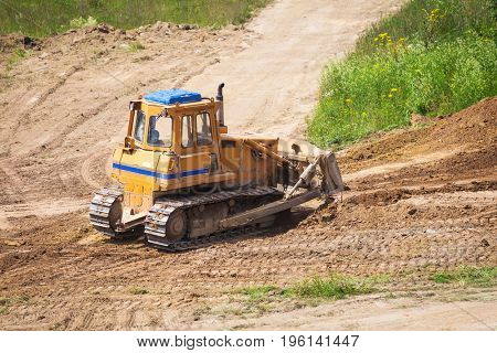 Yellow bulldozer with caterpillar moving ground with scoop