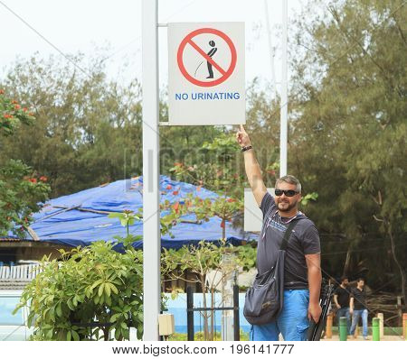 Goa India - March 01 2015: Man showing strange street sign om the road in India