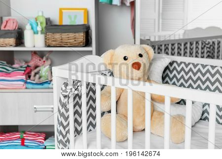 Crib and wardrobe with clothes in light baby room