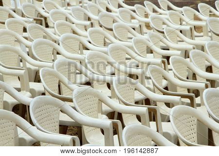 Many white plastic chairs put up for conference