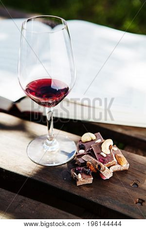 Glass with red wine and pieces of chocolate with nuts and raisins stands on wooden bar on background of open book. Alcoholic drink in glassware with snack
