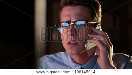Young man using mobile phone while working on computer at night in dark office.