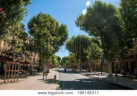 Aix-en-Provence, France - July 09, 2016. Avenue with trees and people in Aix-en-Provence, a lively town in the French countryside. In Bouches-du-Rhone department, Provence region, southeastern France