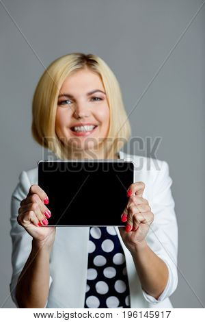 Smiling beautiful model holds tablet