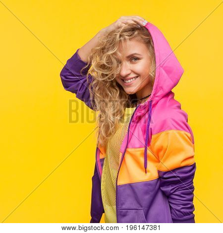Young curly woman in colorful sportive clothing posing happily on orange background
