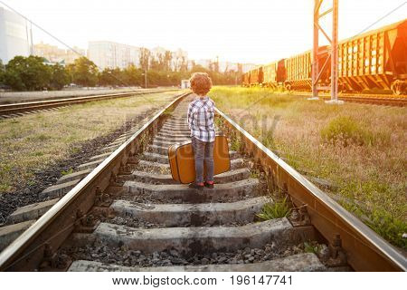 Back view of young boy wearing checkered shirt holding brown suitcase standing on railways.