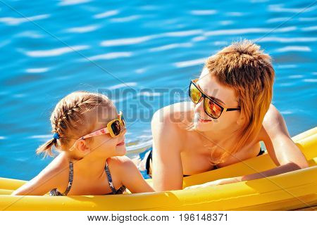 Mother and daughter in sunglasses floating on airbed together.