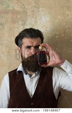Man Posing With Bottle Of Red Liqueur