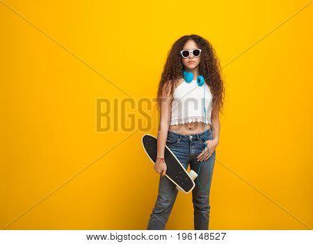 Wavy haired teenage girl standing wearing headphones sunglasses white top jeans holding cruiser board.