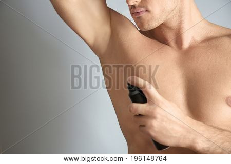 Handsome young man with deodorant on grey background, closeup