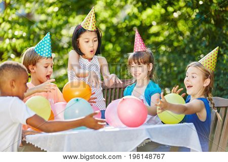 Kids have fun at childrens birthday party in summer in garden