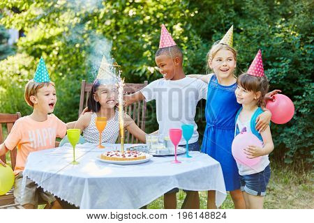 Kids as friends at interracial birthday party with table fireworks