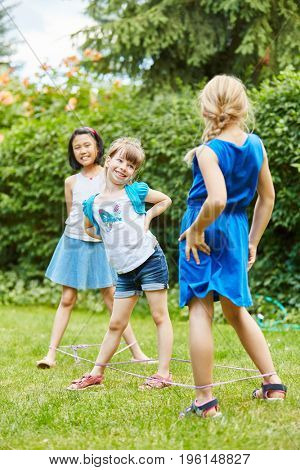 Three girls play as friends chinese jump rope in garden with rubber band