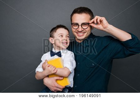 Father wearing glasses embracing son dressed in white shirt with bow tie holding yellow book.