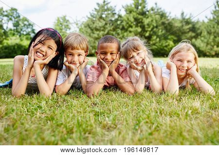Multicultural group of children lie on grass and rest during school trip
