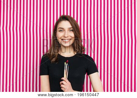 Portrait of woman in casual clothing posing on striped background with paintbrushes.