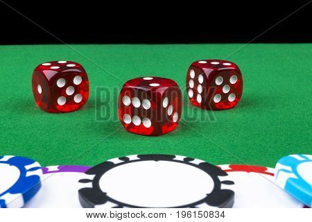 A set of poker chips stack on a green game table with a dice rolls. Black background. risk concept - playing poker in casino. Poker game theme. Red casino dice rolls.