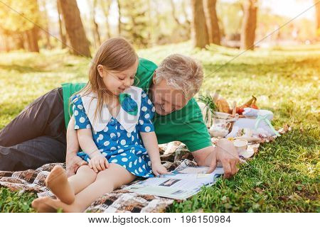 Man with gray hair laying on blanket holding his granddaughter reading magazine on picnic on summer.