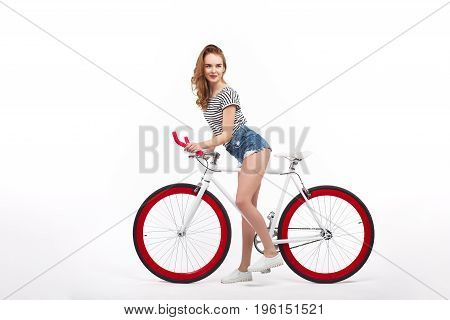 Side view of girl in shorts riding bicycle on white background.