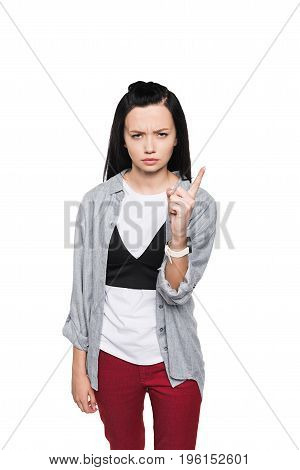 Serious Brunette Girl Pointing Up With Finger And Looking At Camera Isolated On White