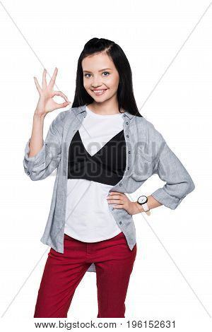 Beautiful Young Brunette Woman Showing Ok Sign And Smiling At Camera Isolated On White