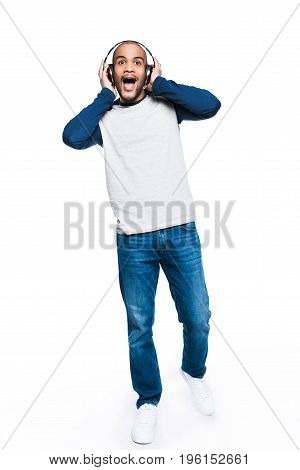 Excited Young African American Man Listening Music In Headphones And Looking Away Isolated On White