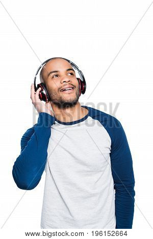 Pensive Young African American Man Listening Music In Headphones And Looking Away Isolated On White