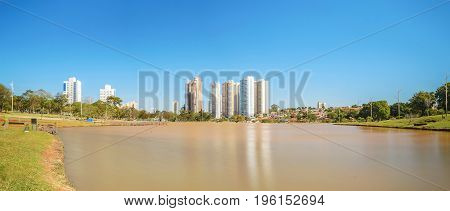 Sunny day at a lake of a park with few buildings on background a amazing clear blue sky and surrounded by nature. Photo at Parque das Nacoes Indigenas in Campo Grande city.