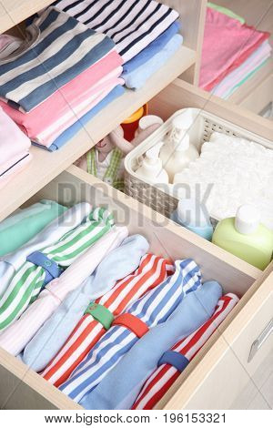 Wardrobe with clothes and necessities in baby room