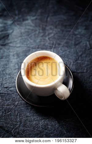 Cup of espresso on a dark blue cloth