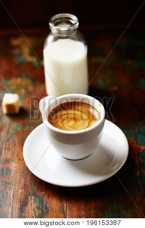 Cup of espresso and a bottle of milk